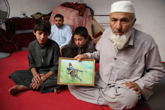 In this Thursday, May 30, 2019 photo, Noor Mohammad, who fled his village in Nangarhar in late April as Islamic State group fighters swept through the area, shows a picture of his son, a soldier in the army who died in Helmand Province fighting the Taliban.