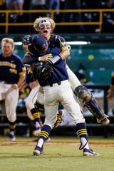 Michigan's Benjamin Keizer, front and Michigan's Joe Donovan celebrate after Michigan defeated UCLA during the ninth inning Sunday.  Michigan won 4-2.