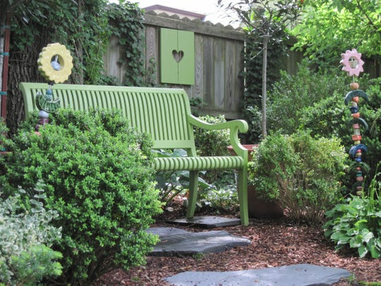A bench painted just the right shade of green is tucked in between a couple of boxwoods in this shade garden. Stepping stones lead the way to the bench -- and support the legs in the mulched bed.