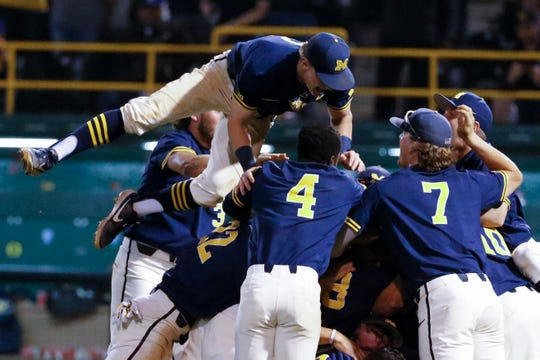 Michigan's players celebrate after Michigan defeated UCLA in Game 3 of the Super Regional Sunday night.