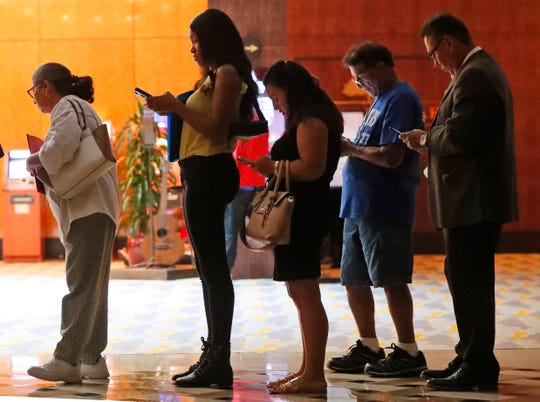 Job applicants wait in line at the Seminole Hard Rock Hotel & Casino Hollywood during a job fair in Hollywood, Fla.