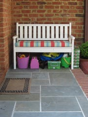 A bench just beside the back door comes in handy when you're changing into and out of garden shoes. Bins under the bench are a good place to stash garden tools.