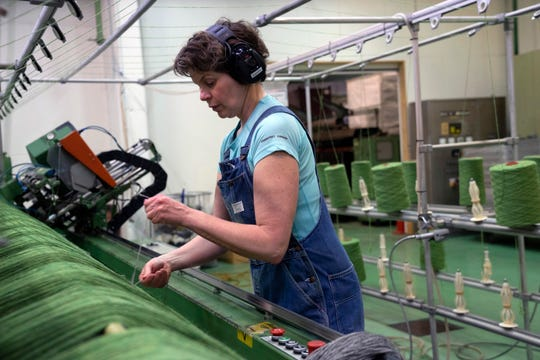 "In this photo taken on Wednesday, April 24, 2019, Asgerdur Jonasdottir, a worker at the Istex wool factory, prepares a large spinning machine with green ""lopi"" yarn, in Reykjavik."