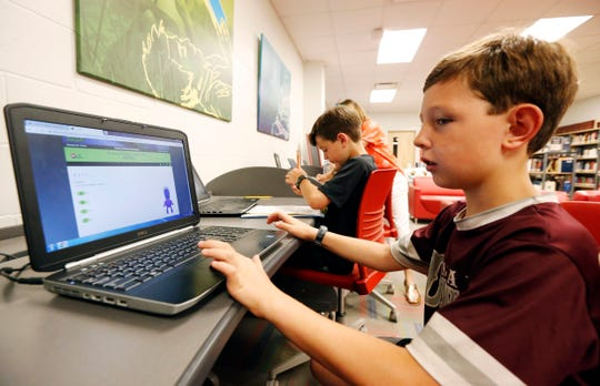 Third-grade student Miles Stidham uses an East Webster High School laptop to do homework in Maben, Miss. The Stidhams are unable to get internet at their home in the country, so they take advantage of the internet in the school's library.
