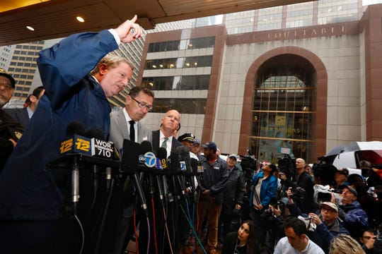 New York Mayor Bill de Blasio, left, Fire Commissioner Daniel Nigro, second left, and Police Commissioner James O'Neill, third left, participate in a press conference about a helicopter that crashed into the Equitable Building, at right, in New York, Monday.