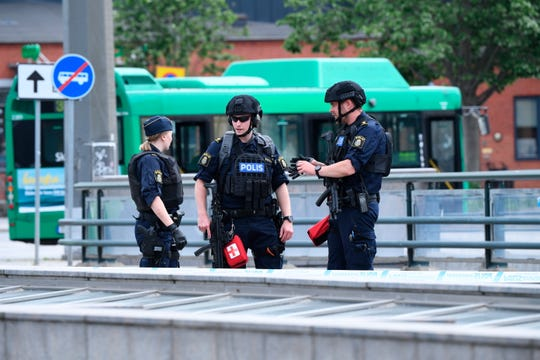 Police offices attend the scene after police shot and wounded a man at Malmo central station.