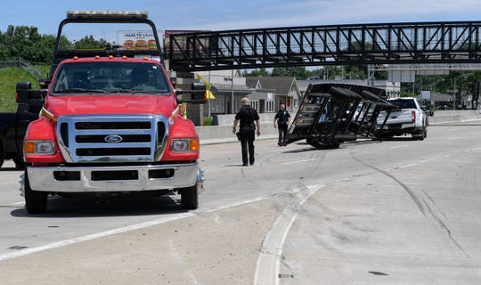 Emergency workers clear an accident on the eastbound Lloyd Expressway after a vehicle carrier, transporting pick-up trucks from Nashville, overturned coming off of 41N ramp on the expressway Monday, June 10, 2019.