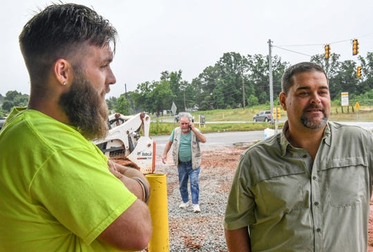 Dylon Harward, left, talks about being adopted by Lee Davis, right, while Jimmy L. Davis walks up at the site of a future BP gas station at exit 40 in Powdersville. The family works together on projects closer to home so they can spend more time together.