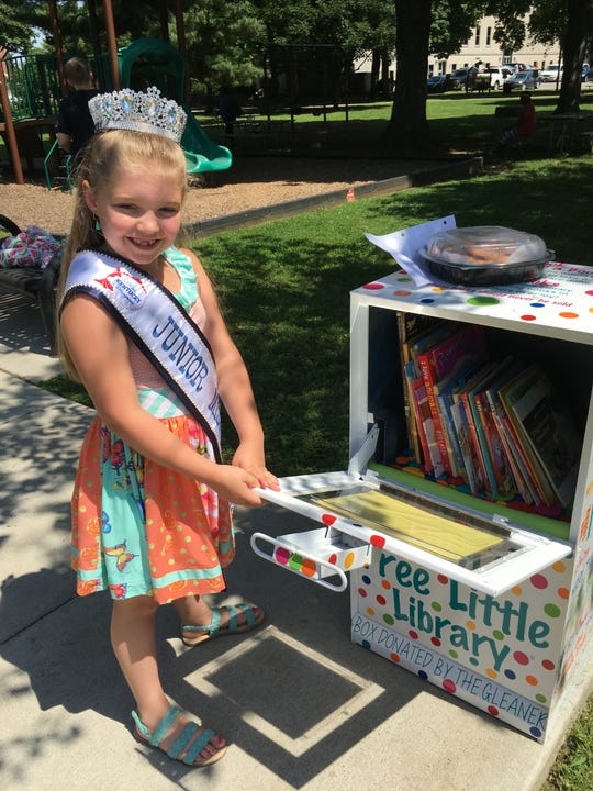 Ellen Chaney, who is enthusiastic about pageants and reading, poses with her Little Free Library near the playground in Central Park.
