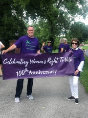 "Henderson County Judge-executive Brad Schneider and event organizer Jule McClellan hold a banner for Sunday's walk celebrating 100 years of women's right to vote in the United States. (Former Henderson Mayor and longtime educator Joan Hoffman can be seen ""photo bombing"" in the background.)"