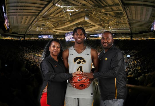 In this photo that Bakari Evelyn (against a full Carver-Hawkeye Arena backdrop) during his Iowa visit, he is flanked by his mother, Sandee Stone, and older brother, Tino Fernandez.
