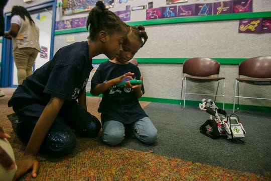 Girls Scout Cecil Khadijah looks over the shoulder of her sister and fellow Girl Scout Tete Minatagbe Diakite Kariessy learning to control robots with a remote iPhone at the Math and Science Canter at Camp Dellwoood, Indianapolis, Wednesday, May 29, 2019.