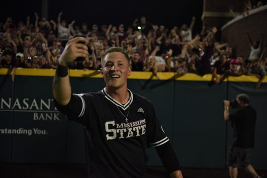 Elijah MacNamee records on his cell phone as fans celebrate in the background after Mississippi State's 8-1 win over Stanford in Game 2 of the Super Regionals in Starkville on Sunday, June 9, 2019.