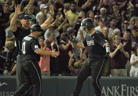 Dustin Skelton celebrates with assistant coach Kyle Cheesebrough after a base-clearing triple in the third inning of Game 2 of the Super Regionals against Stanford on Sunday, June 9, 2019, in Starkville.