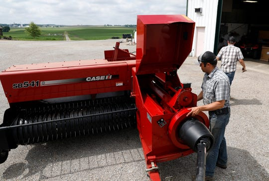 Jon Miller, left, and his cousin Andrew Miller prepare a bailer Thursday morning, June 6, 2019, at their family's farm in Pleasant Township.