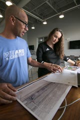 Droo Callahan, director of sports at the Legacy Center Sports Complex, and Kristen Althouse, director of volleyball, discuss architectural renderings of a proposed new center for volleyball and basketball courts Monday, June 10, 2019.
