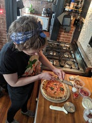 Pizza Lupo sous chef Katie Smith shaves cheese over a finished pizza