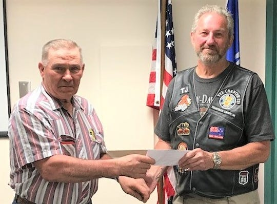 Jim Weisner (left), Manitowoc County Deputy Sheriff's and Constables Association president, presents a $750 check to Terry Johnson, Vietnam Veterans of America Manitowoc County, to assist with bringing  the Vietnam Veterans Memorial Wall to Manitowoc County.