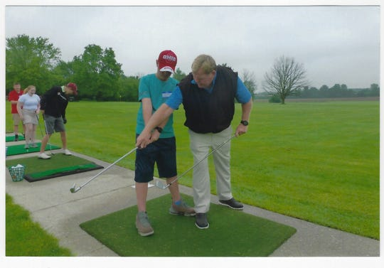 Golf pro Steve Grimes Instructs Seth Smith of Upper Sandusky during the Heart of Ohio Junior Golf Association's clinic held last week at Miracle Driving Range in Marion.