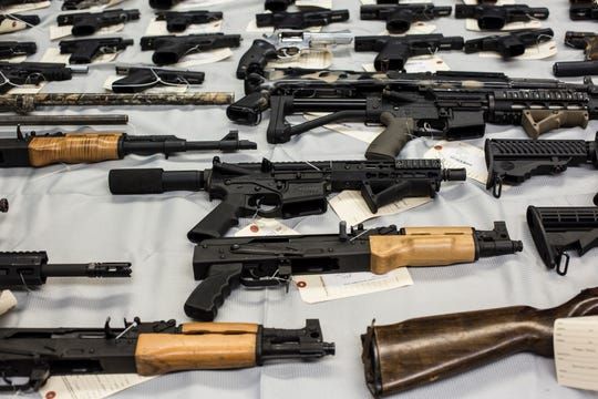 Multiple guns are seen on display as Memphis Police Director Michael Rallings speaks during a press conference about two recent operations by MPD's Organized Crime Unit, June 10, 2019.