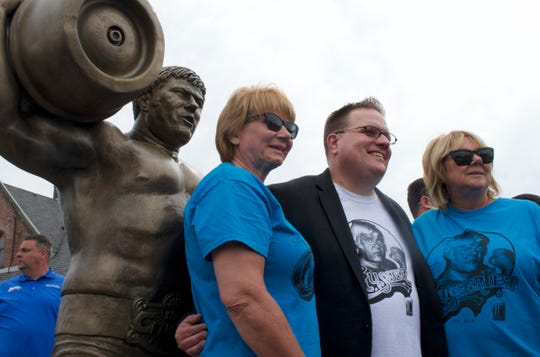 "Daughters of Reggie ""Da Crusher"" Lisowski Sherri Brozoski (left) and Dawn Lisowski (right) along with South Milwaukee Mayor Erik Brooks (center) pose with the life-sized bronze statue at Crusherfest June 8."