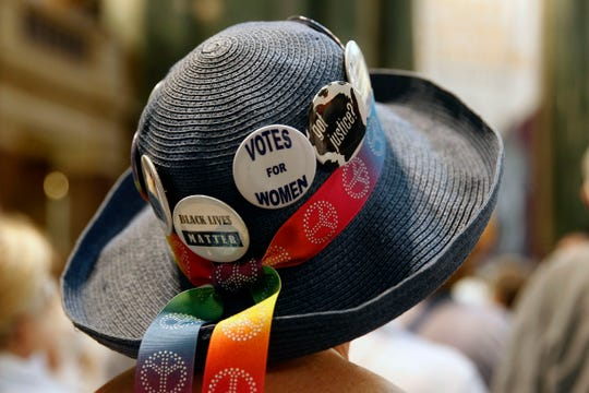A woman attending the celebration of the 100-year anniversary of the Women's Suffrage Movement displays her political leanings on her hat.