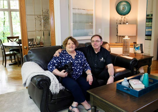 Homeowners Joan and Tony Beck relax with Gizmo, their daughter's dog, in their Waukesha home.