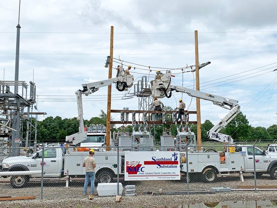 North Arkansas Electrical Cooperative employees assemble a temporary electrical substation at the Southland Substation site Friday afternoon.