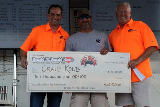 """The 2019 Ronald McDonald House Big Bass Tournament Champion Craig Kolb (center) receives the Big Check for $10,000 for his """"Big Bass"""" of 6.56 pounds at the Awards Ceremony of the 2019 Ronald McDonald House Big Bass Tournament at the Ike Hamilton Exposition Center in West Monroe on Sunday, June 9."""