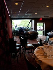 A Nissan Sentra is seen in the dining room of Ruth's Chris Steakhouse at the Parsippany Hilton Sunday night after an 87-year-old woman crashed through from the parking lot. June 9, 2019.