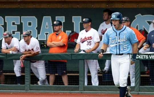 North Carolina's Michael Busch (15) celebrates after scoring a run during the first inning of an NCAA super regional baseball game against Auburn in Chapel Hill, N.C., Sunday, June 9, 2019. (AP Photo/Ben McKeown)