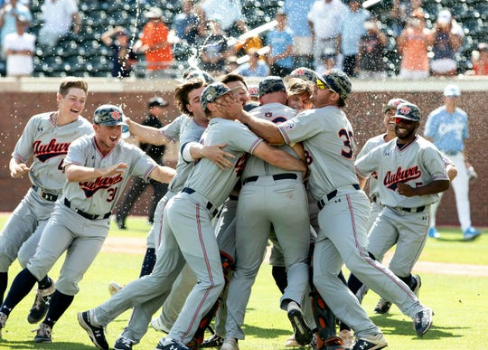 Auburn celebrates their victory over North Carolina in an NCAA college super regional baseball game in Chapel Hill, N.C., Monday, June 10, 2019.