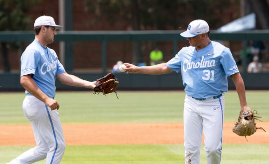 North Carolina pitcher Joey Lancellotti (31) hands the ball to North Carolina's Connor Ollio, left, during the first inning of a super regional against Auburn in Chapel Hill, N.C., Monday, June 10, 2019.
