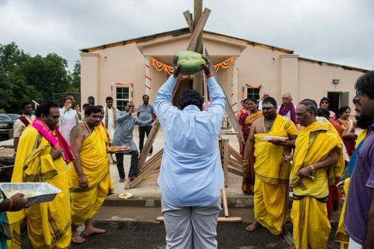 Members of the Hindu temple smash white pumpkins which symbolizes the removal of the evil eye and other negative energy during the Pran Pratistha (dignity of life) ceremony at the Hindu Temple of Montgomery in Pike Road, Ala., on Sunday, June 9, 2019.
