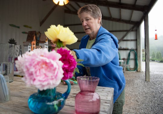 Iris City Gardens co-founder and co-owner Macey McCullough places fresh cut peonies in a vase in the garden shop on May 17, 2019.
