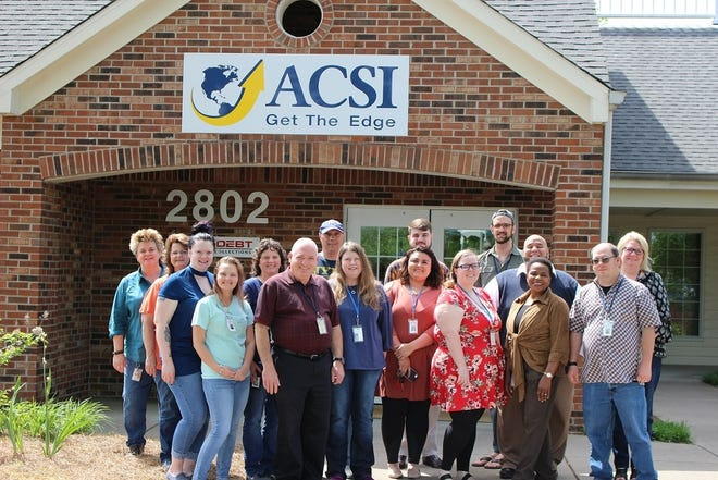 A group of ACSI employees gather in front of the office.