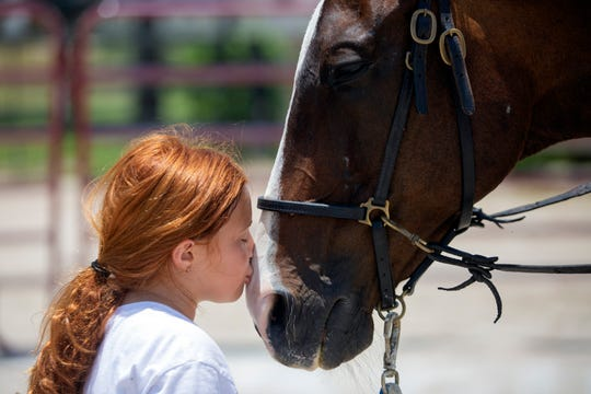 Giada DiSarro kisses Jackson as they rest between rides during a summer horse camp hosted by Track to Trail Thoroughbreds, Monday, June 10, 2019, at the Pine Ridge Equestrian OTTB Training Facility and Education Center in North Naples.