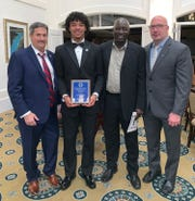 Golden Gate's Jordan Williams (second from left) shows his plaque from the National Football Foundation Collier County chapter's annual banquet at Kensington Country Club in February 2019. Williams is with (from left to right) chapter vice president Tom Stuart, his dad Tony, and Golden Gate football coach Mike DiGrigoli.