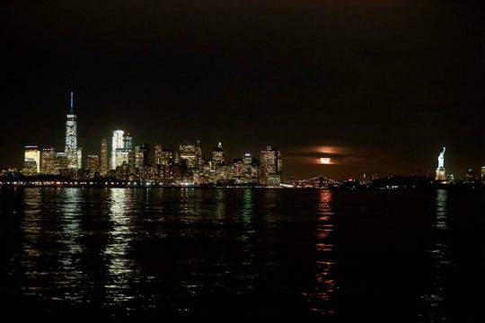 The supermoon, center, rises behind clouds near the Lower Manhattan skyline, including, the Statue of Liberty seen from the Port Liberty neighborhood of Jersey City, N.J.,