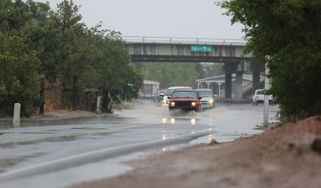Vehicles slow down while crossing a flooded portion of West Boutz Road in Las Cruces on Monday, June 10, 2019.