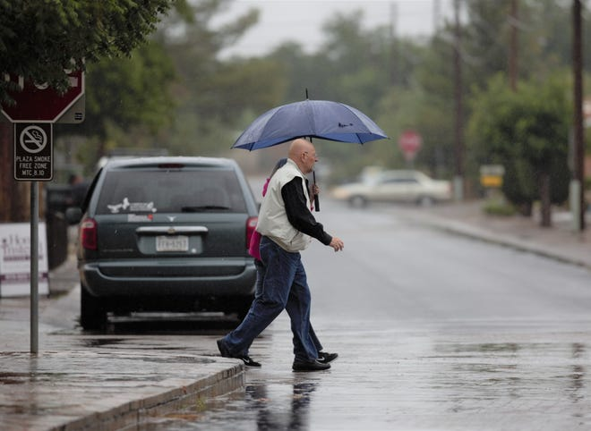 Pat Byrne, foreground, and Faye Clements of Texas walk through the rain-slicked streets of Mesilla on Monday, June 10, 2019, as rainfall continues.