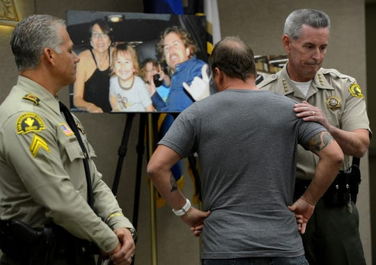 "FILE - In this Nov. 7, 2014, file photo, Michael McStay is consoled by San Bernardino County Sheriff John McMahon as he reacts before talking to the media about his late brother's family at a news conference in San Bernardino, Calif. A jury verdict will be read in the case of a Southern California man charged with killing a family of four and burying their bodies in the desert. The verdict will be read Monday, June 10, 2019, in court in San Bernardino in the quadruple murder case against 62-year-old Charles ""Chase"" Merritt. (Jennifer Cappuccio Maher/The Orange County Register via AP, File)"