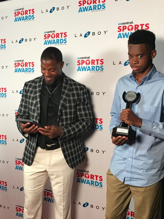 Arizona Cardinal David Johnson, left, looks at a gift from Brophy athlete Adonis Watt, who is holding his Courage Award trophy during the azcentral Sports Awards Sunday, June 9, 2019.