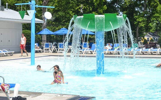 Children play under the fountain in the heated pool at Lakeside's Grindley Aquatic & Wellness Campus.