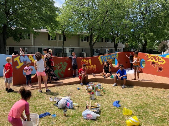 Kids helped paint a new play area at Dulhut Village over the weekend.