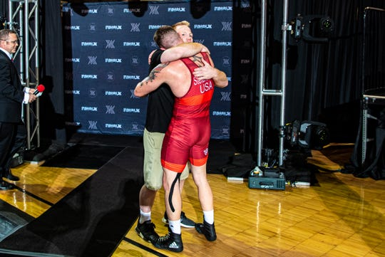 John Stefanowicz (red singlet) hugs his younger brother, Chance Marsteller, after winning the Final X championships at Rutgers. Stefanowicz advances to the World Championships in September with an eye on the 2020 Olympics.