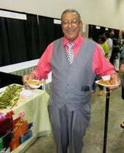 "Classic ticket holder Lemon Jenkins attends the fund raiser every year. ""I enjoy tasting everything,"" Jenkins said as he juggles plates of fried shrimp, fried potatoes and  sausage."