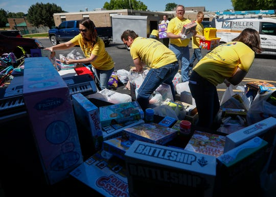 Volunteers with Miller Engineering unload toys, games, and bikes outside of Great Circle on Monday, June 10, 2019.