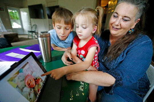 In this Thursday, June 6, 2019, photo, Victory points to her baby photo, as her brother Richard and her mother Amie Schofield look on, at their home in Ogden, Utah. (AP Photo/Rick Bowmer)