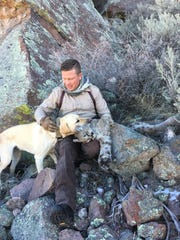 A DWR conservation officer works with a K9 to track wildlife.